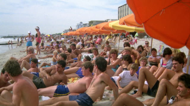 WIDE ANGLE OF SEVERAL PEOPLE LYING ON BEACH BELOW YELLOW AND ORANGE UMBRELLAS. SEE LIFEGUARD IN BACKGROUND. SEE PEOPLE RUBBING SUNTAN LOTION ON OR LOOKING AT SOMETHING OFF SCREEN.