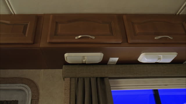 UP ANGLE OF RV KITCHEN CABINETS, WITH BLUE SCREEN OUTSIDE WINDOW. RV JOSTLED, PLATES FALL FROM CABINETS. BEDROOM IN BACKGROUND. ACCIDENTS.