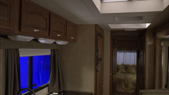 MEDIUM ANGLE OF RV KITCHEN, WITH BLUE SCREEN OUTSIDE WINDOW. RV JOSTLED, PLATES FALL FROM CABINETS. BEDROOM IN BACKGROUND. ACCIDENTS.