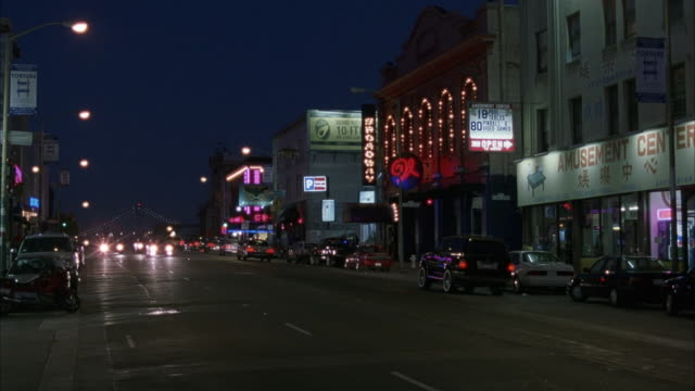WIDE ANGLE OF BROADWAY STREET IN NORTH BEACH. SEE STOREFRONT. SEE MARQUEE THAT SAYS BROADWAY ACROSS STREET. CARS DRIVING TOWARD CAMERA ON STREET. NIGHTCLUBS. STRIP CLUBS.