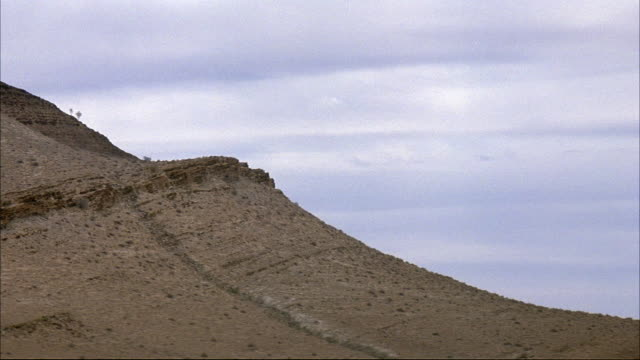 MEDIUM ANGLE OF SIDE OF DESERT MOUNTAIN. SEE SCATTERED PLANTS OR SHRUBS. SEE BLUE AND WHITE SKY IN BACKGROUND. COULD BE MIDDLE EAST.