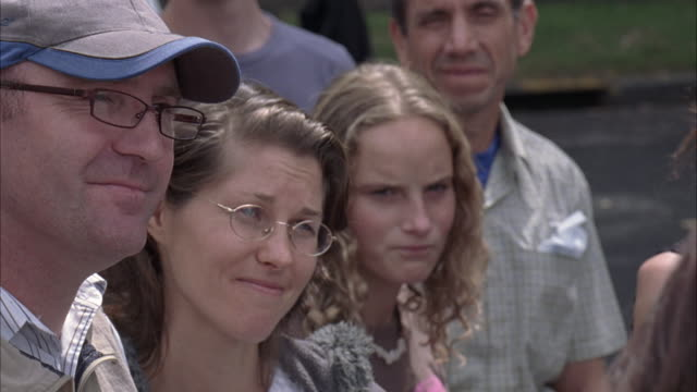 CLOSE ANGLE, REACTION SHOT OF A MAN, WOMAN, AND YOUNG WOMAN IN A CROWD. COULD BE A FAMILY. MAN AND WOMAN SMILE AND THEN LOOK DOWN. MAN AND WOMAN WEAR GLASSES AND MAN HAS BASEBALL CAP. YOUNG GIRL HAS BLONDE HAIR. OTHER MEN AND WOMEN IN BACKGROUND.