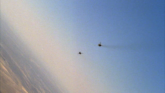 TRACKING SHOT OF TWO KFIR JETS FLYING AWAY FROM CAMERA, BOTH DO BARREL ROLL AND DIVE TOWARDS DESERT GROUND, NEG CUT. MIDDLE EAST.