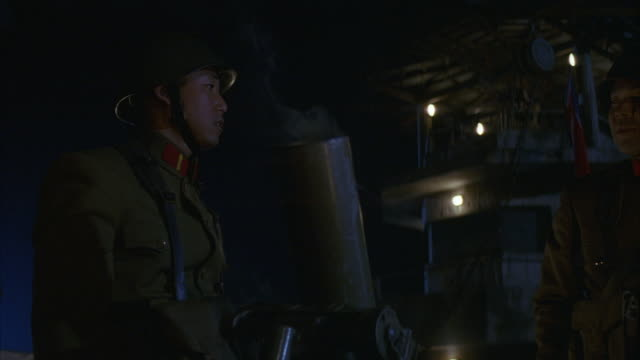 MEDIUM ANGLE OF TWO NORTH KOREAN SOLDIERS DRESSED IN OLIVE GREEN UNIFORMS AND HELMETS. SOLDIERS INSERT SHELL INTO MORTAR GUN AND FIRE THE WEAPON. GUARD TOWER VISIBLE  IN BACKGROUND. COMBAT. MILITARY BASES.