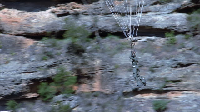 AERIAL VIEW OF STUNT OF PERSON HANGING IN AIR FROM PARACHUTE-LIKE DEVICE. INSTEAD OF PARACHUTE SEE STRAPS ATTACH TO METAL WIRES WHICH EXTEND OUT OF FRAME. COULD BE MAN IN MILITARY UNIFORM.