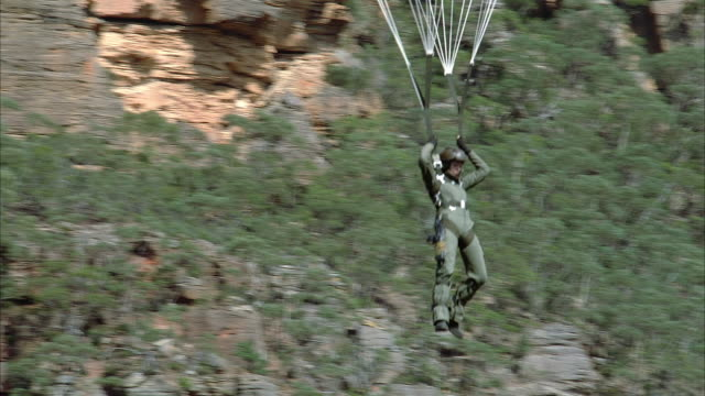 AERIAL VIEW OF STUNT OF PERSON HANGING IN AIR FROM PARACHUTE-LIKE DEVICE. INSTEAD OF PARACHUTE SEE STRAPS ATTACH TO METAL WIRES WHICH EXTEND OUT OF FRAME.
