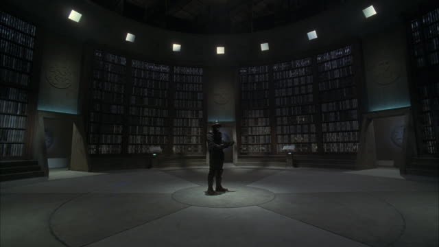 WIDE ANGLE OF ARMED MAN IN UNIFORM STANDING IN CENTER OF CIRCULAR LIBRARY. SEE FLOOR TO CEILING BOOKSHELVES, THREE ENTRANCES, AND RADIATION HAZARD SYMBOL ON FLOOR.