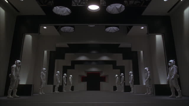 WIDE ANGLE OF LONG FUTURISTIC HALL. UNUSUAL BLACK AND WHITE WALLS WITH A CROSS ENTRYWAY IN BACKGROUND. SEE MASKED MEN IN WHITE SUITS WITH SWORDS. COULD BE GUARDS OR SOLDIERS OR MILITARY PERSONNEL.