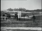 Wright brothers and crew bringing their airplane out of a barn and starting the engine for US Army demonstration / Fort Myer Virginia United States