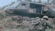 UH1B helicopter landing in newly cleared field 101st Airborne Division soldiers boarding Huey and sergeant sitting at open Huey side door / Vietnam