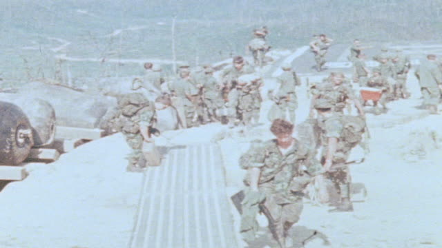 MONTAGE 101st Airborne Division soldiers carrying and setting down supplies at fire support base / Vietnam