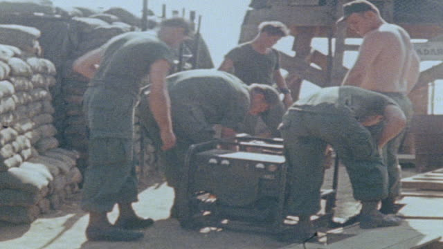 MONTAGE 101st Airborne Division soldiers unloading supplies from landing area at fire support base atop mountain / Vietnam
