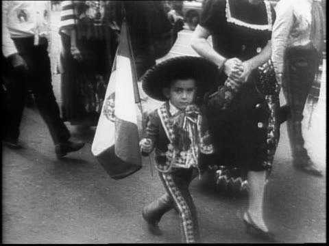 132nd anniversary of independence / a parade with marching band and flags is proceeding down a street / people in traditional costume / small boy...