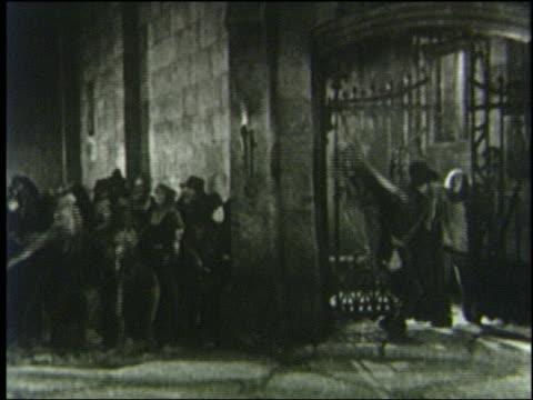 B/W 1800s angry crowd runs thru gate shouting at night