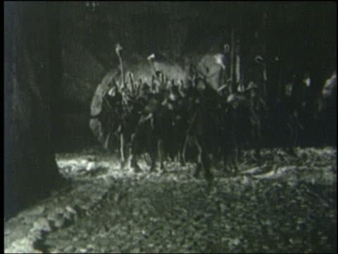 B/W 1800s crowd carrying torches + weapons runs thru archway toward camera at night