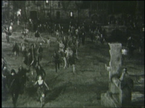 B/W 1800s high angle crowd carrying torches + weapons runs toward camera in Paris street at night