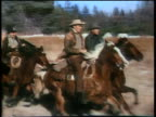 1860s tracking shot group of cowboys riding running horses on plain / Actors in front of group are Randolph Scott (light brown hat and brown jacket) and Forrest Tucker (grey hat and dark blue jacket)
