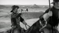 1870s reenactment medium shot man in US Cavalry uniform blowing bugle, riding on horseback beside flag-bearer