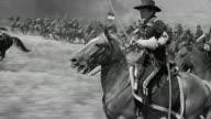 1870s reenactment US Cavalry officer (Errol Flynn) on horseback points saber, leads charge of men into battle