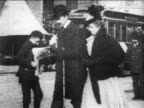 B/W 1890s slow motion paperboy selling newspapers to people on Broadway sidewalk / NYC / newsreel