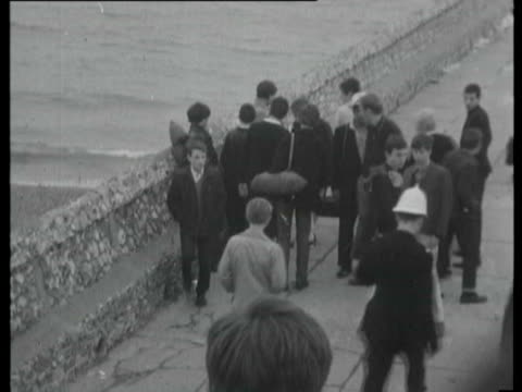 18May1965 B/W MONTAGE Young people running off beach police making arrests and moving people on / United Kingdom