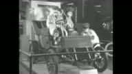 1900s era vintage car with three moving mannequins and another in a duster coat turning the starter crank / Note exact month/day not known