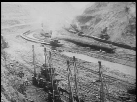 B/W 1900s high angle wide shot freight trains carrying dirt in Panama Canal construction / documentary