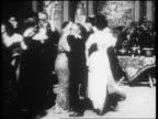 B/W 1900s slow motion people in formalwear waltzing at party