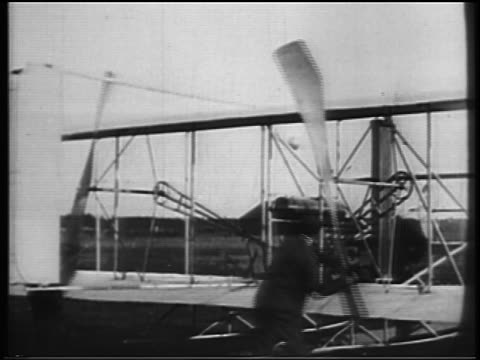 B/W 1900s Wright brothers starting propeller on biplane / documentary