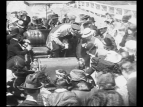 1904era automobiles move in parade on Los Angeles street as spectators look on / woman in Native American costume rides horse as another woman...