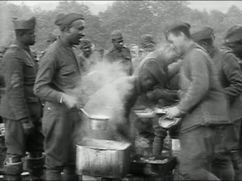 1910s black and white US soldiers of allblack troop in mess line / World War I / Europe