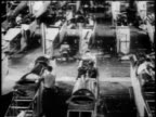 B/W 1910s high angle men working on fuselages of warplane in airplane factory / WWI