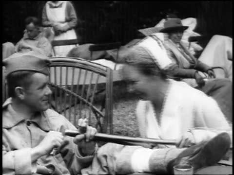 B/W 1910s nurse sitting talking with wounded soldier as he whittles end of crutch outdoors / doc