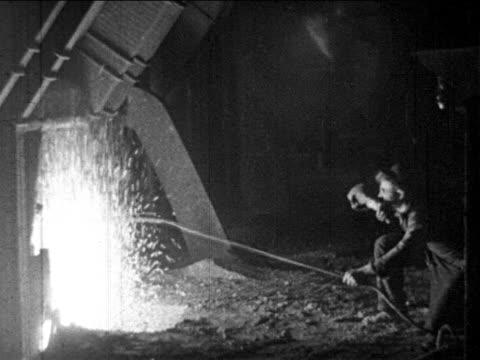 B/W 1910s steelworker pokes blazing furnace with pole / newsreel