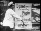 B/W 1910s woman plastering poster advertising Liberty Bonds / World War I / newsreel