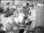B/W 1910s woman playing piano + smiling at camera / crowd of people in background / documentary