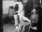 B/W 1910s woman vacuuming carpet as man reads newspaper in rocking chair / documentary