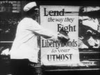 B/W 1910s women pasting up poster to buy Liberty Bonds / WW I / documentary