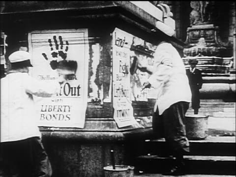 B/W 1910s women pasting up posters to buy Liberty Bonds / WW I / documentary
