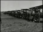 WORLD WAR I FIGHTER AIRPLANES VS United States soldiers wheeling out biplane fighter aircraft from hangar row of biplanes on field ace pilot Edward...