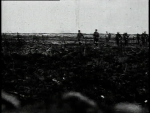 1910s WS WWI British raid armed soldiers walking through muddy field with prisoners / Europe