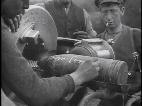 1910s MS WWI soldier writing with chalk on large artillery shell as it is being loaded / France