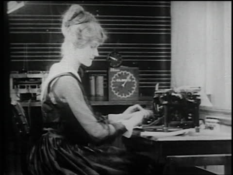 B/W 1910s/20s MS PROFILE woman reading document + typing at desk / timer in background