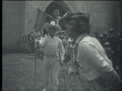 B/W 1910s/20s slow motion man in white cowboy hat whipping cigarette out of  woman's mouth