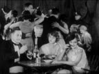B/W 1920s 2 flappers man smoking at table in speakeasy / couples dancing in background / Prohibition