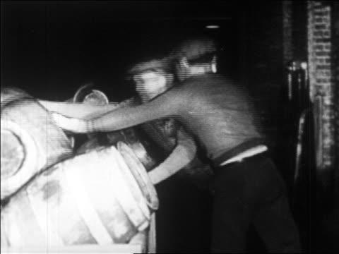 B/W 1920s 2 men loading barrels of bootleg liquor onto pile / Prohibition / newsreel