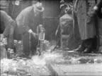 B/W 1920s authorities smashing bottles of bootleg liquor on curb / Prohibition / newsreel