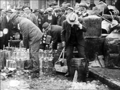 B/W 1920s authorities smashing bottles of bootleg liquor on street as crowd watches / Prohibition
