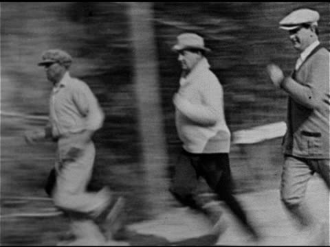 BOXING Boxer Jack Dempsey running down woodland road w/ others Dempsey boxing in outdoor ring w/ unidentified fighter and referee
