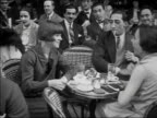1920s B/W MS Man and two women at outdoor cafe laughing and smoking / Paris, France